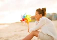 thoughtful-young-woman-colorful-windmill-toy-sitting-beach-evening-44274305